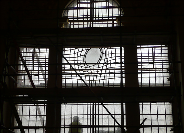 The new stained glass window glimpsed through scaffolding