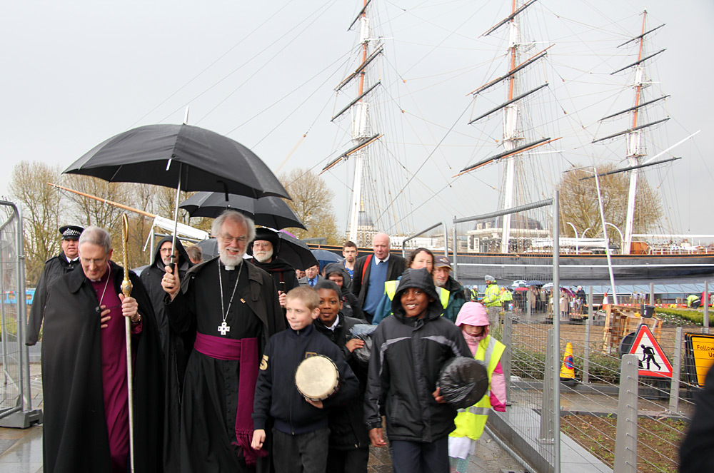 Archbishop walks with pilgrims in front of the Cutty Sark, Greenwich