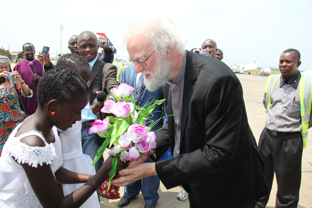 A welcomer greets the Archbishop with flowers